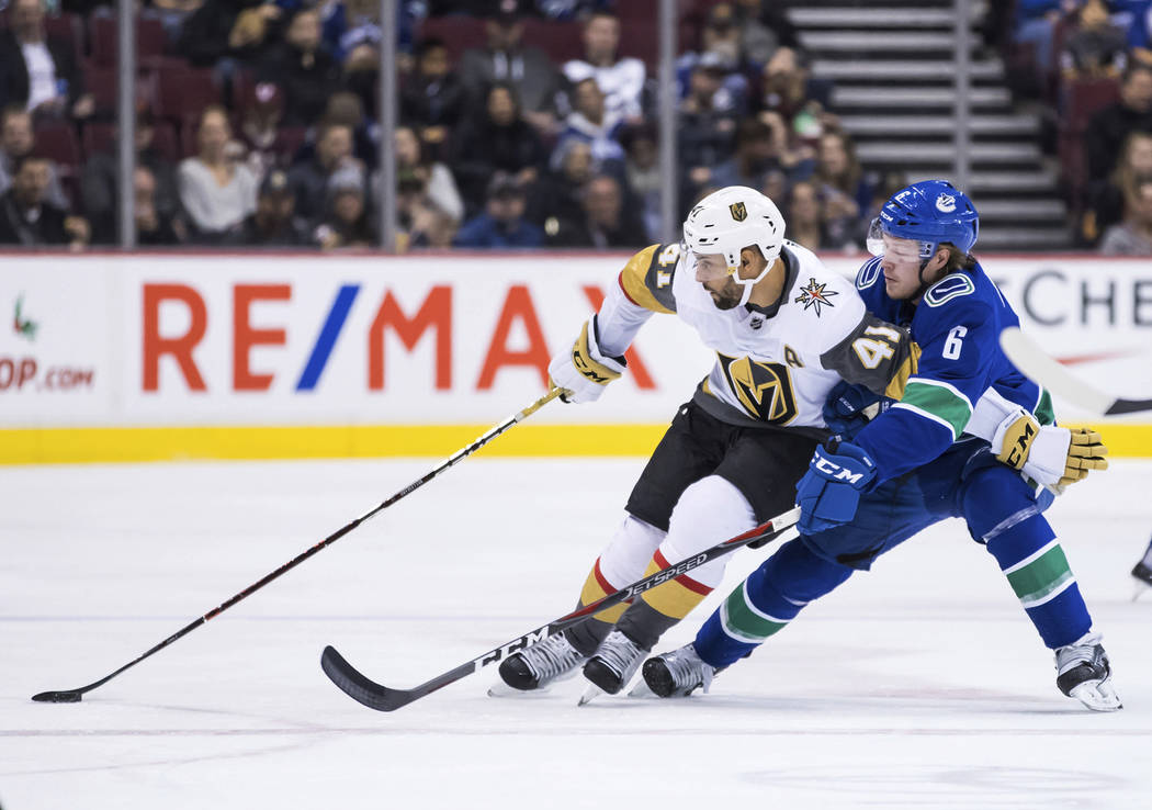 Vegas Golden Knights' Pierre-Edouard Bellemare (41) tries to hold off Vancouver Canucks' Brock Boeser (6) while skating with the puck during the first period of an NHL hockey game Thursday, Nov. ...