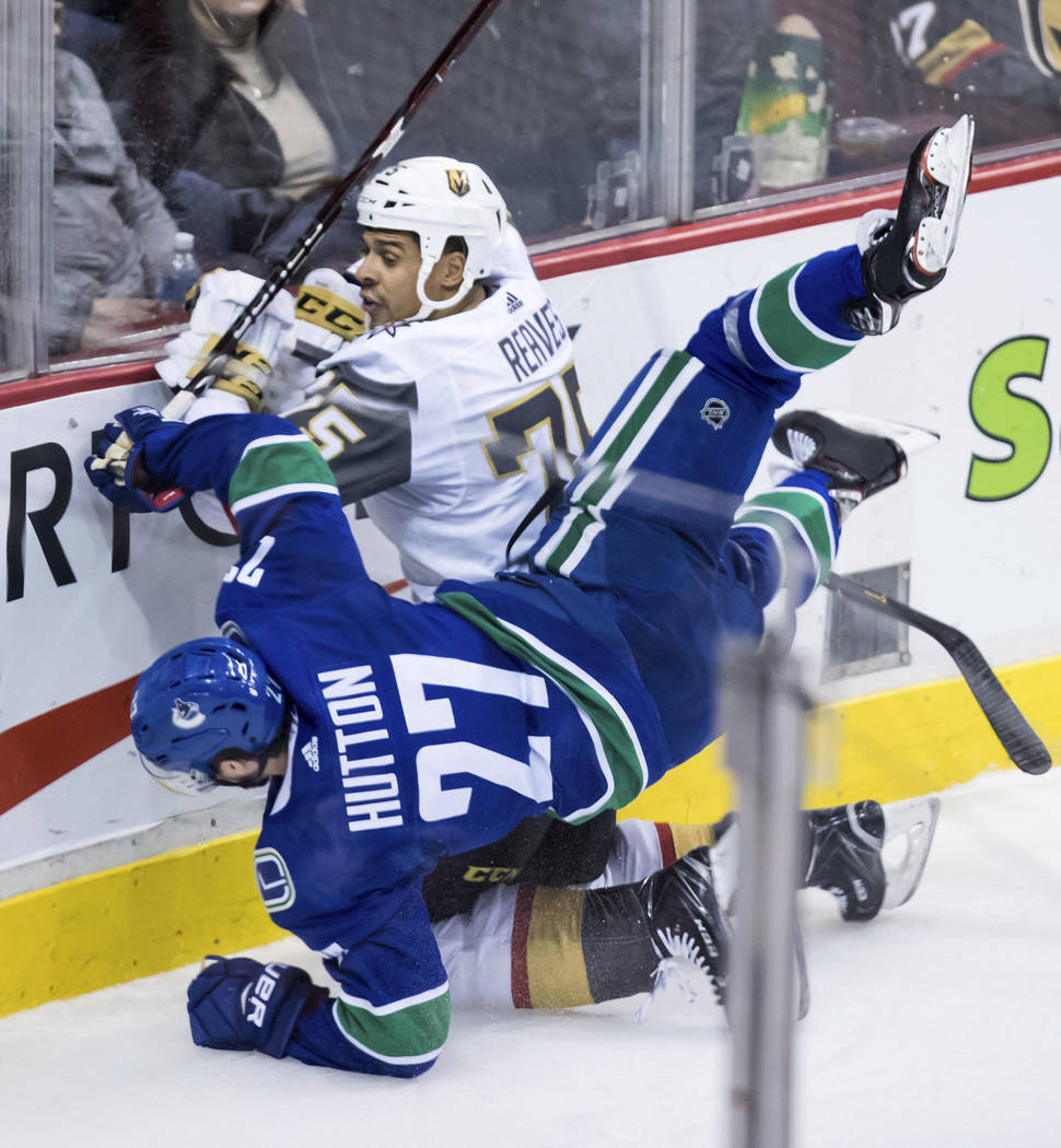 Vancouver Canucks' Ben Hutton (27) and Vegas Golden Knights' Ryan Reaves (75) collide during the second period of an NHL hockey game Thursday, Nov. 29, 2018, in Vancouver, British Columbia. (Darry ...