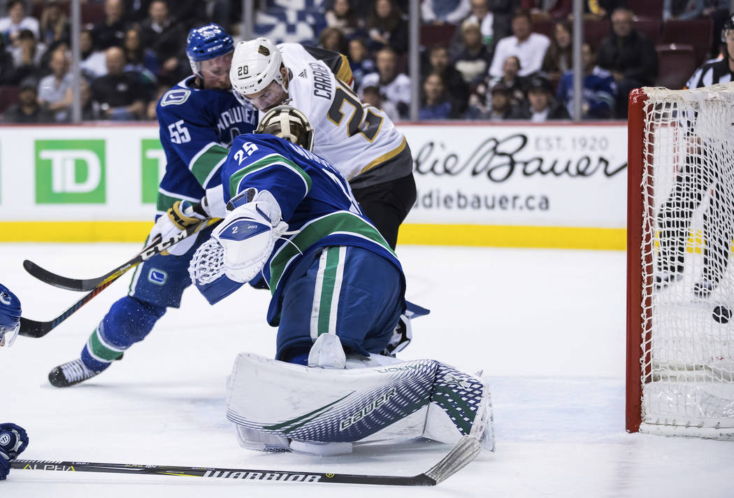 Vegas Golden Knights' William Carrier, back right, scores against Vancouver Canucks goalie Jacob Markstrom, of Sweden, while being checked by Alex Biega (55) during the first period of an NHL hock ...
