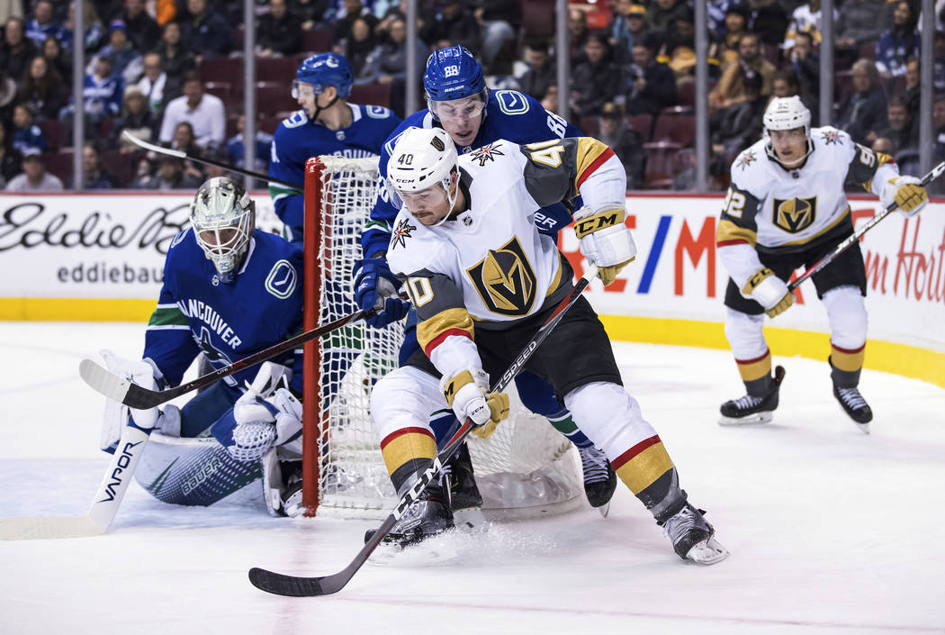 Vegas Golden Knights' Ryan Carpenter (40) skates around the net with the puck behind Vancouver Canucks goalie Jacob Markstrom, left, of Sweden, while being checked by Adam Gaudette (88) during the ...