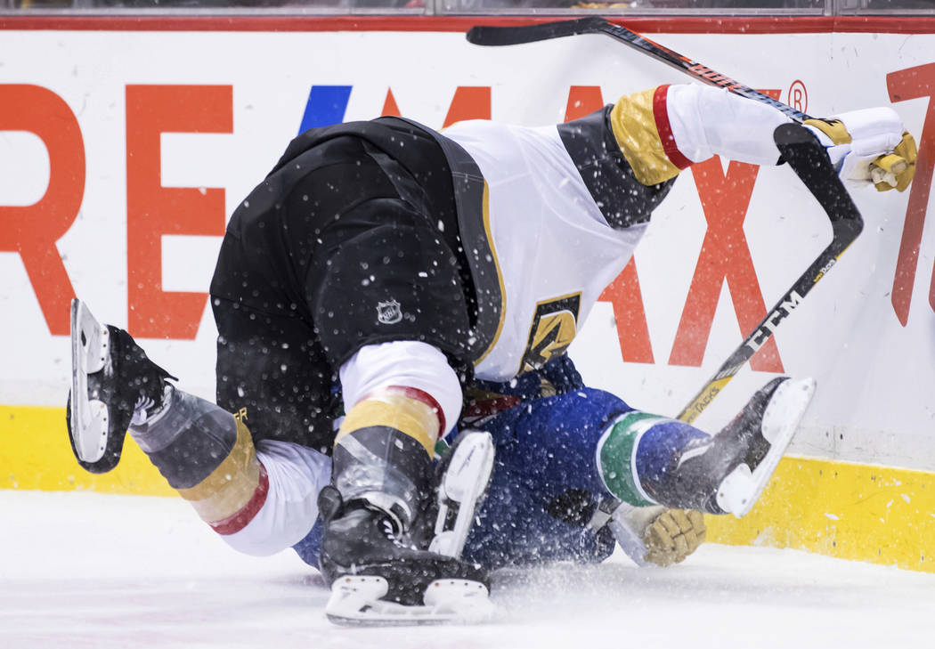 Vegas Golden Knights' William Carrier, top, and Vancouver Canucks' Alex Biega fall to the ice after colliding during the first period of an NHL hockey game Thursday, Nov. 29, 2018, in Vancouver, B ...