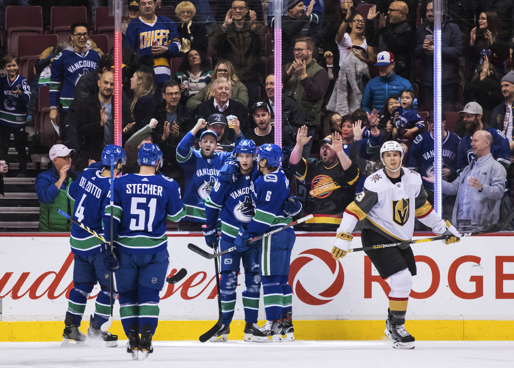 Vancouver Canucks' Michael Del Zotto, Troy Stecher, Elias Pettersson and Brock Boeser, from left, celebrate Boeser's goal as Vegas Golden Knights' Brayden McNabb skates to the bench during the fir ...