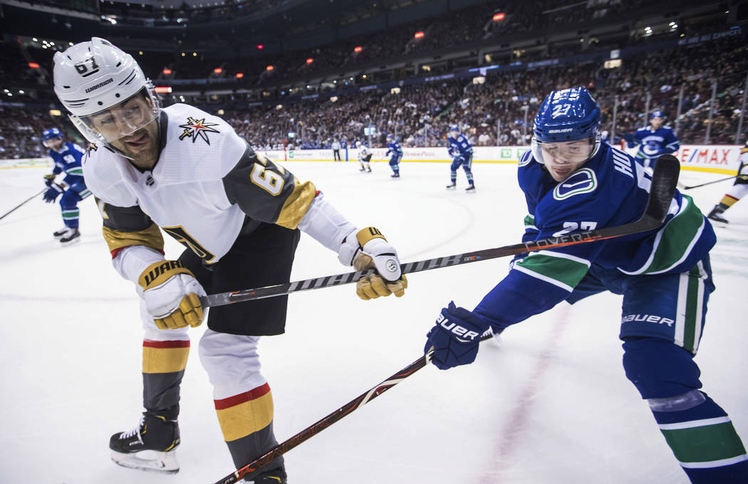 Vegas Golden Knights' Max Pacioretty, left, passes the puck past Vancouver Canucks' Ben Hutton during the first period of an NHL hockey game Thursday, Nov. 29, 2018, in Vancouver, British Columbia ...