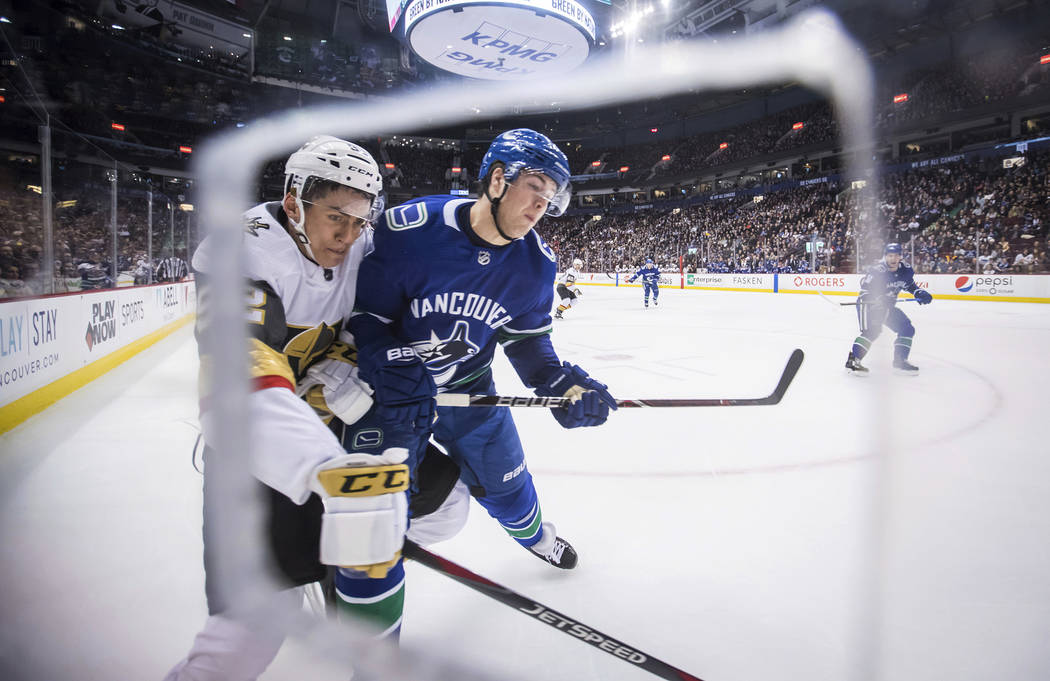 Vegas Golden Knights' Tomas Nosek, left, of the Czech Republic, is checked by Vancouver Canucks' Ben Hutton during the first period of an NHL hockey game Thursday, Nov. 29, 2018, in Vancouver, Bri ...