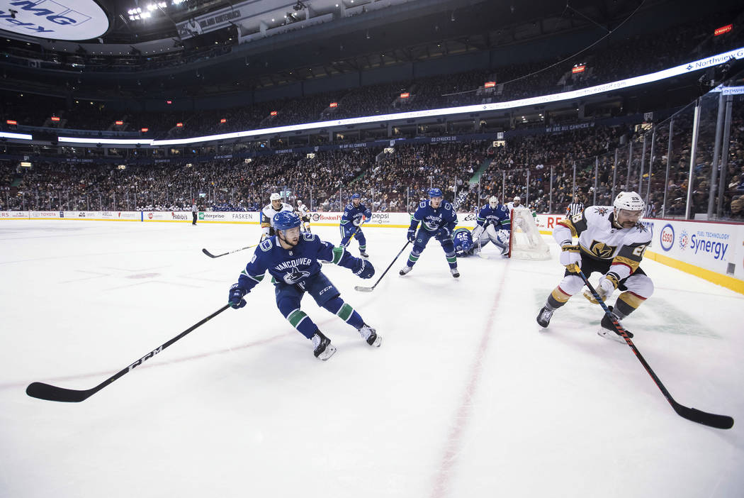 Vegas Golden Knights' William Carrier, right, skates with the puck while being watched by Vancouver Canucks' Brendan Leipsic, left, during the first period of an NHL hockey game Thursday, Nov. 29, ...