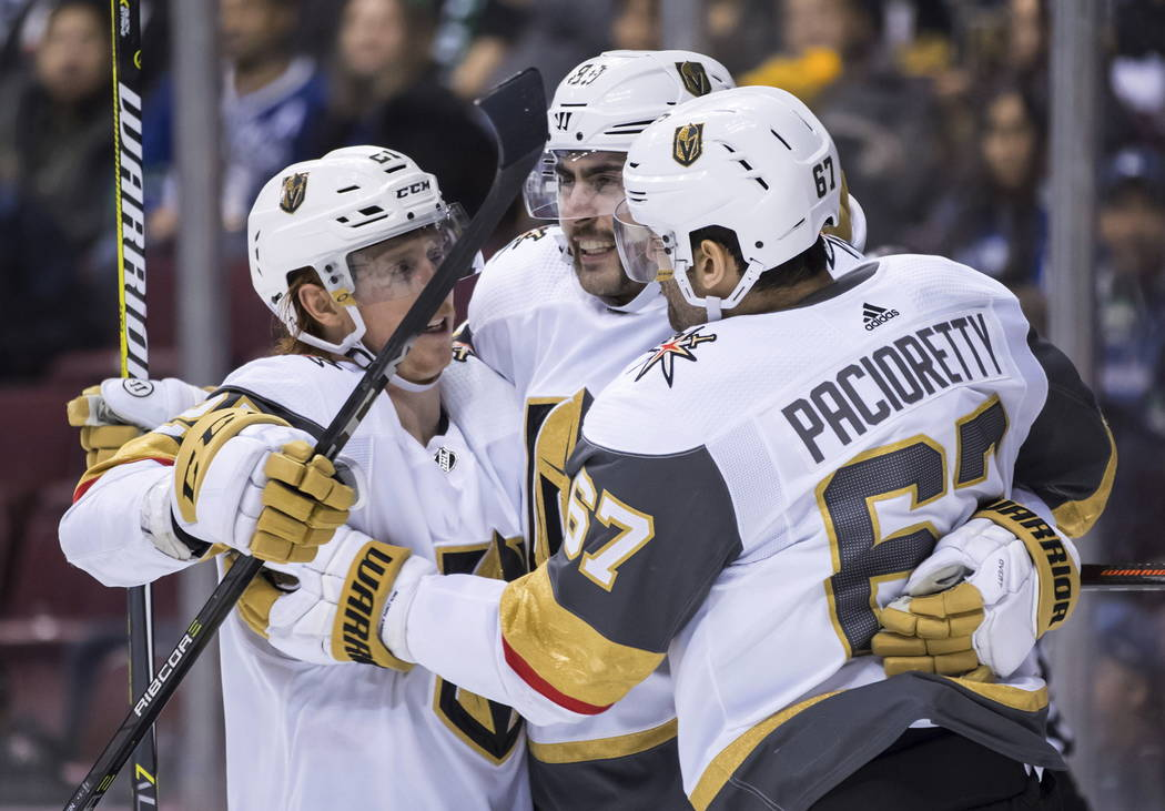 Vegas Golden Knights' Cody Eakin, Alex Tuch and Max Pacioretty, from left, celebrate Pacioretty's second goal against the Vancouver Canucks, during the third period of an NHL hockey game Thursday, ...