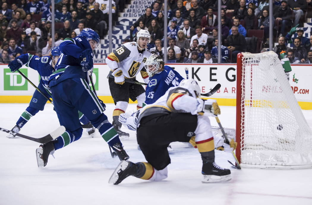 Vegas Golden Knights' William Karlsson, front, of Sweden, scores against Vancouver Canucks goalie Jacob Markstrom (25), of Sweden, as Ben Hutton, left, and Golden Knights' Reilly Smith (19) watch ...