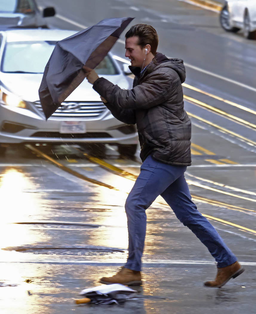 A man struggles in the wind and rain crossing a Financial District street Thursday, Nov. 29, 2018, in San Francisco. A storm moving into California on Thursday brought rain that threatened to unle ...