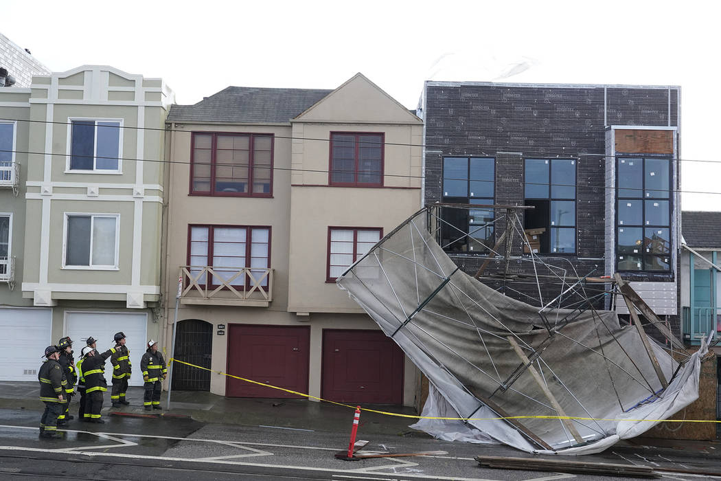 Firefighters look over the scene where scaffolding was blown down on Taraval Street during stormy weather on Thursday, Nov. 29, 2018, in San Francisco. A storm moving into California on Thursday b ...