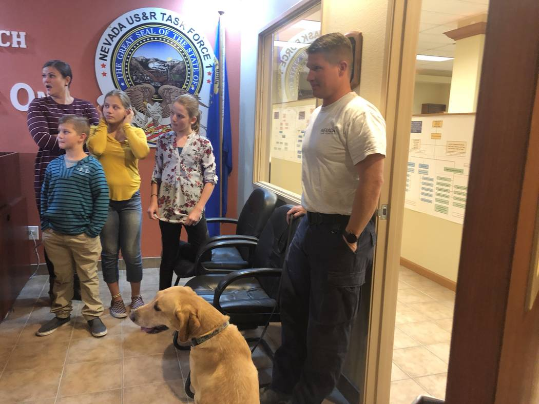 Dexter, a Labrador Retriever, sits next to her handler, Chris Burr, and his family at the Nevada Task Force 1 headquarters on Thursday, November, 29, 2018. Dexter was one of four dogs trained in h ...