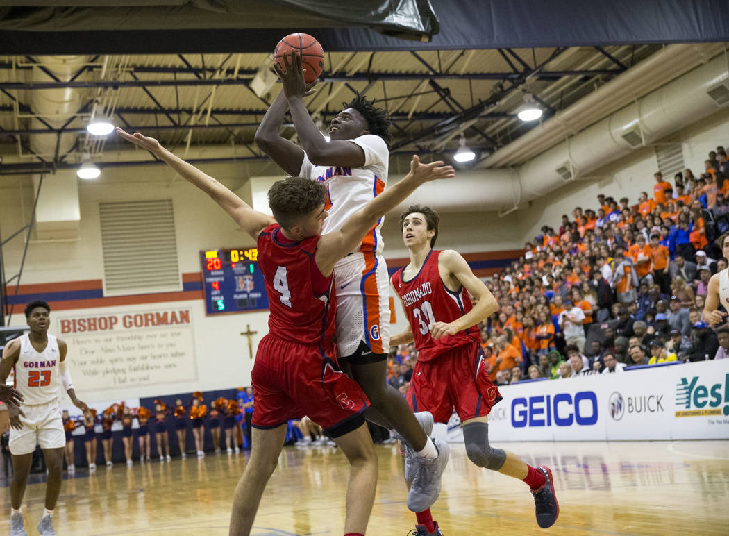 Bishop Gorman's Will McClendon (1) shoots over Coronado's Nick Walters (4) during the first half of a varsity basketball game at Bishop Gorman High School in Las Vegas on Thursday, Nov. 29, 2018. ...
