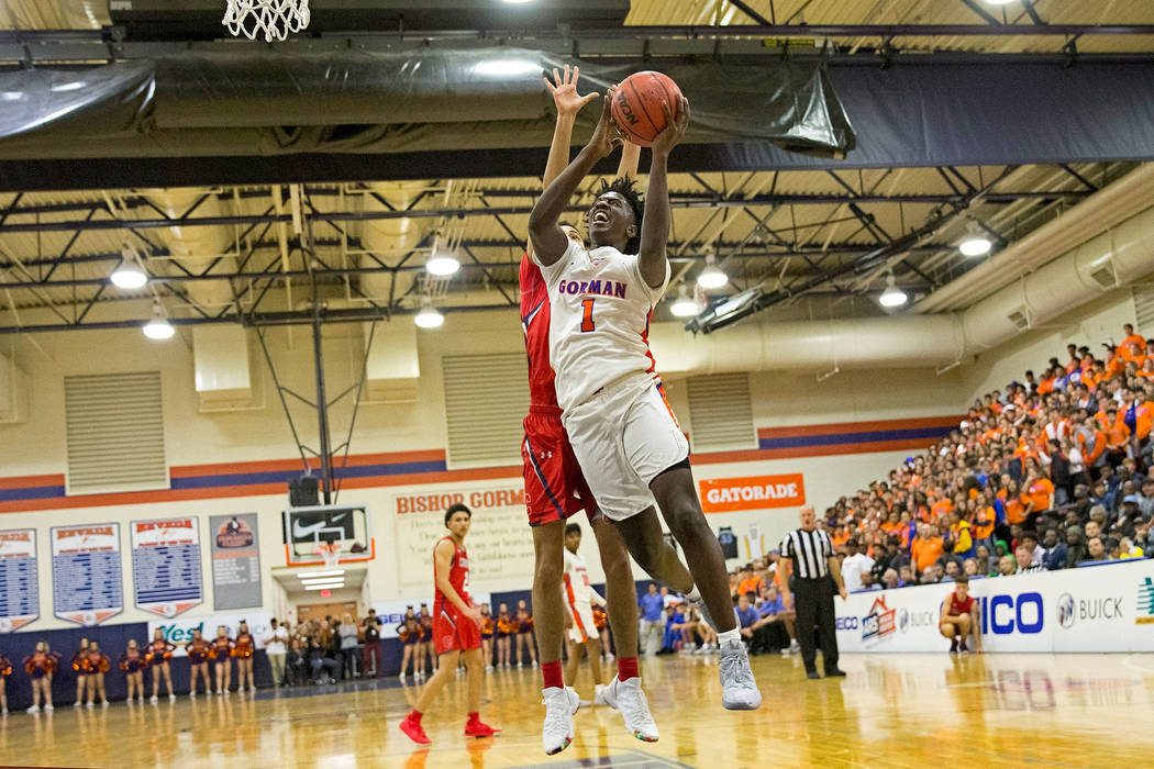 Bishop Gorman's Will McClendon (1) goes up for a shot in front of Coronado's Max Howard (21) during the first halfof a varsity basketball game at Bishop Gorman High School in Las Vegas on Th ...