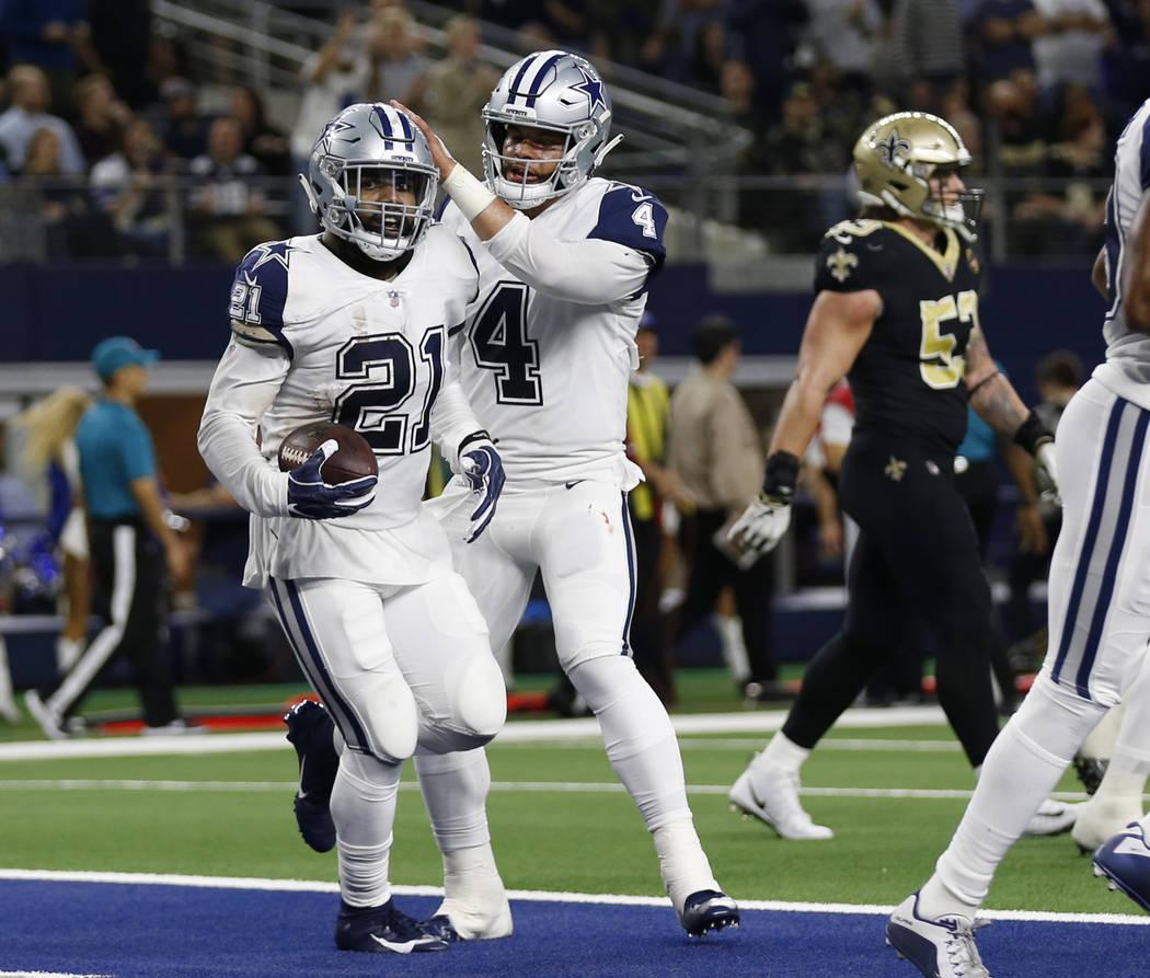Dallas Cowboys running back Ezekiel Elliott (21) celebrates his touchdown against the New Orleans Saints with quarterback Dak Prescott (4) in the first half of an NFL football game, in Arlington, ...