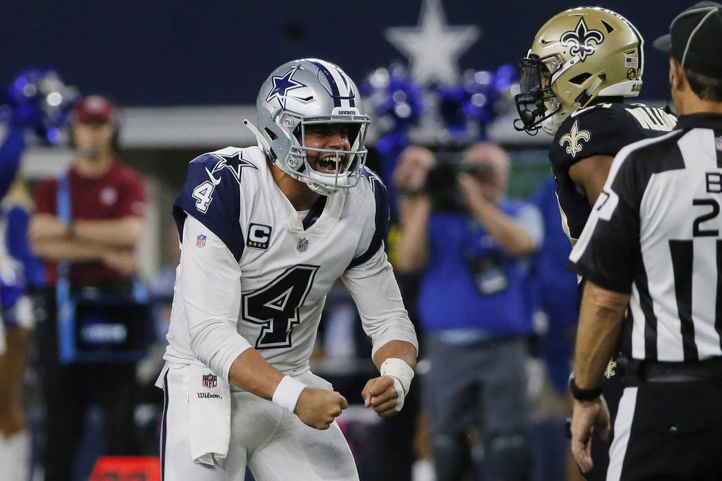 Dallas Cowboys quarterback Dak Prescott (4) celebrates after a run play against the New Orleans Saints during the second half of an NFL football game, in Arlington, Texas, Thursday, Nov. 29, 2018. ...