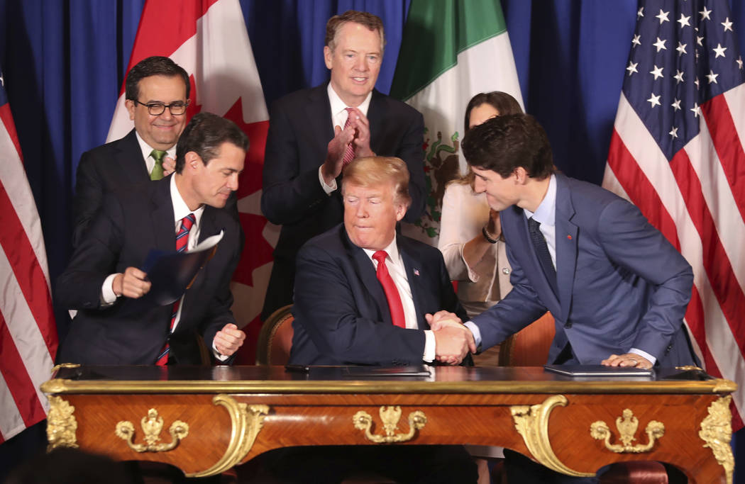 President Donald Trump, center, shakes hands with Canada's Prime Minister Justin Trudeau as Mexico's President Enrique Pena Nieto looks on after they signed a new United States-Mexico-Canada Agree ...