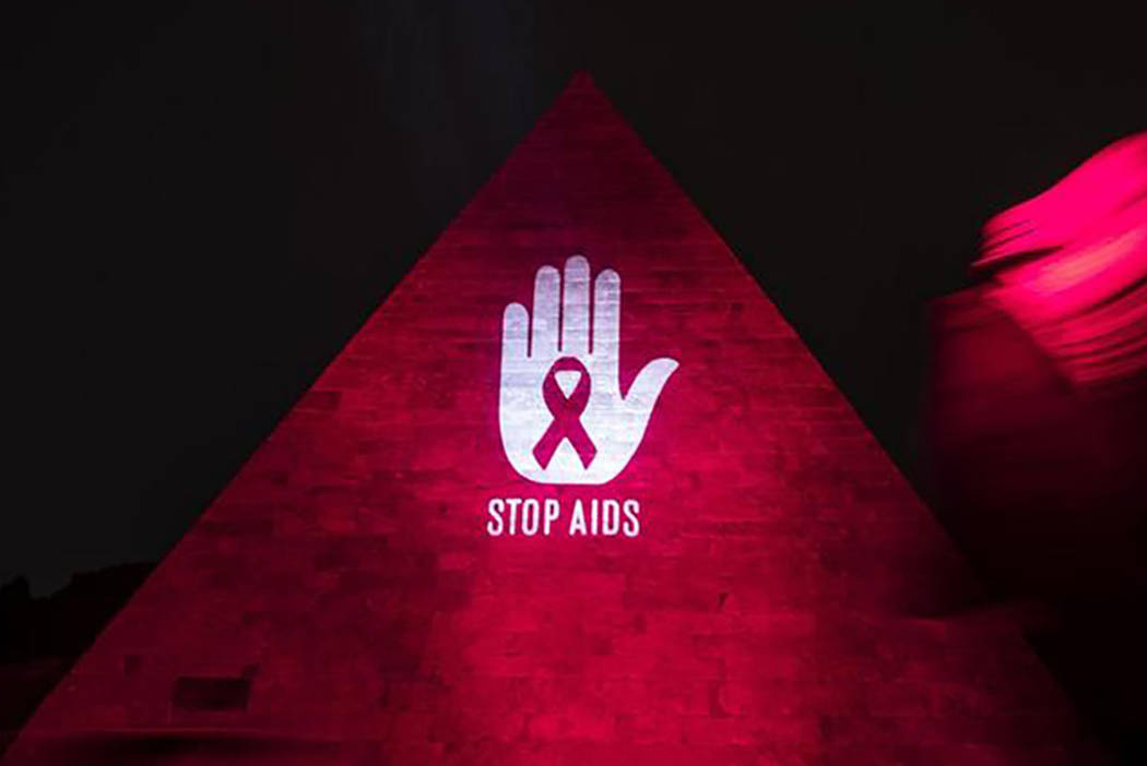 The Pyramid of Cestius is illuminated in red for the World AIDS Day, in Rome. Friday, Nov. 30 2018. (Angelo Carconi/ANSA via AP)