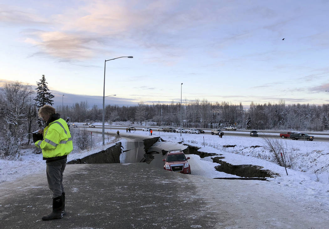 A car is trapped on a collapsed section of the offramp of Minnesota Drive in Anchorage, Friday, Nov. 30, 2018. Back-to-back earthquakes measuring 7.0 and 5.8 rocked buildings and buckled roads Fri ...