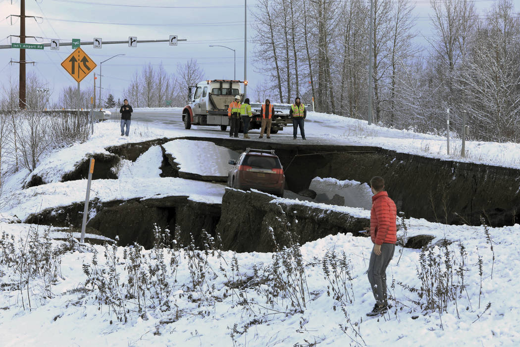Highway workers and spectators look at a car stuck on a section of an off-ramp that collapsed during an earthquake Friday morning, Nov. 30, 2018 in Anchorage, Alaska. The driver was not injured at ...
