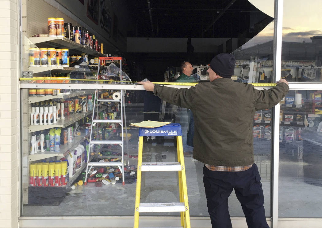 Dennis Keeling measures for a broken window at an auto parts store in Anchorage, on Friday, Nov. 30, 2018. Back-to-back earthquakes measuring 7.0 and 5.8 rocked buildings and buckled roads Friday ...