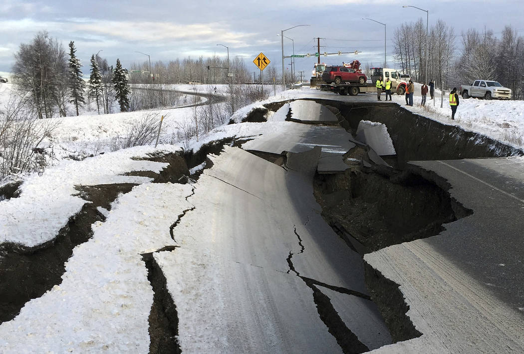 A tow truck holds a car that was pulled from on an off-ramp that collapsed during a morning earthquake on Friday, Nov. 30, 2018, in Anchorage, Alaska. The driver was not injured attempting to exit ...