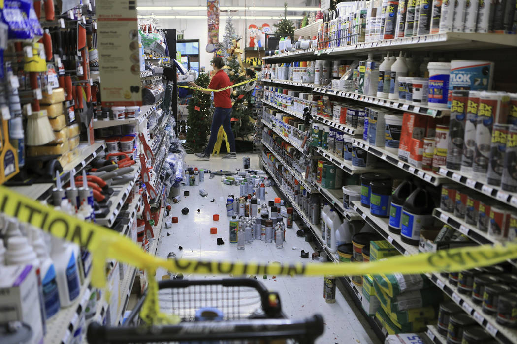 An employee walks past a damaged aisle at Anchorage True Value hardware store after an earthquake, Friday morning, Nov. 30, 2018, in Anchorage, Alaska. Tim Craig, owner of the south Anchorage stor ...