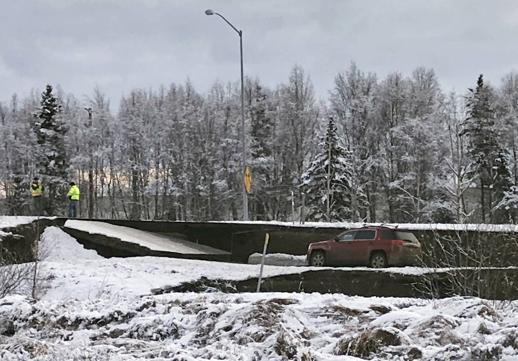 A car is trapped on a collapsed section of the offramp off of Minnesota Drive in Anchorage, Friday, Nov. 30, 2018. Back-to-back earthquakes measuring 7.0 and 5.8 rocked buildings and buckled roads ...