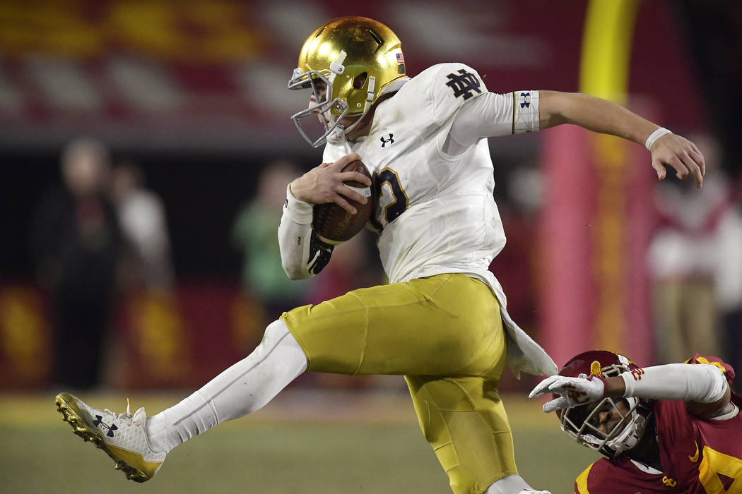 Notre Dame quarterback Ian Book, left, avoids a tackle by Southern California cornerback Isaiah Langley during the second half of an NCAA college football game Saturday, Nov. 24, 2018, in Los Ange ...