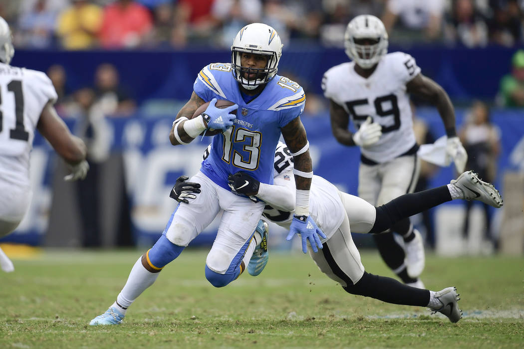 Los Angeles Chargers wide receiver Keenan Allen carries as Oakland Raiders defensive back Leon Hall hauls him down during the second half of an NFL football game Sunday, Oct. 7, 2018, in Carson, C ...
