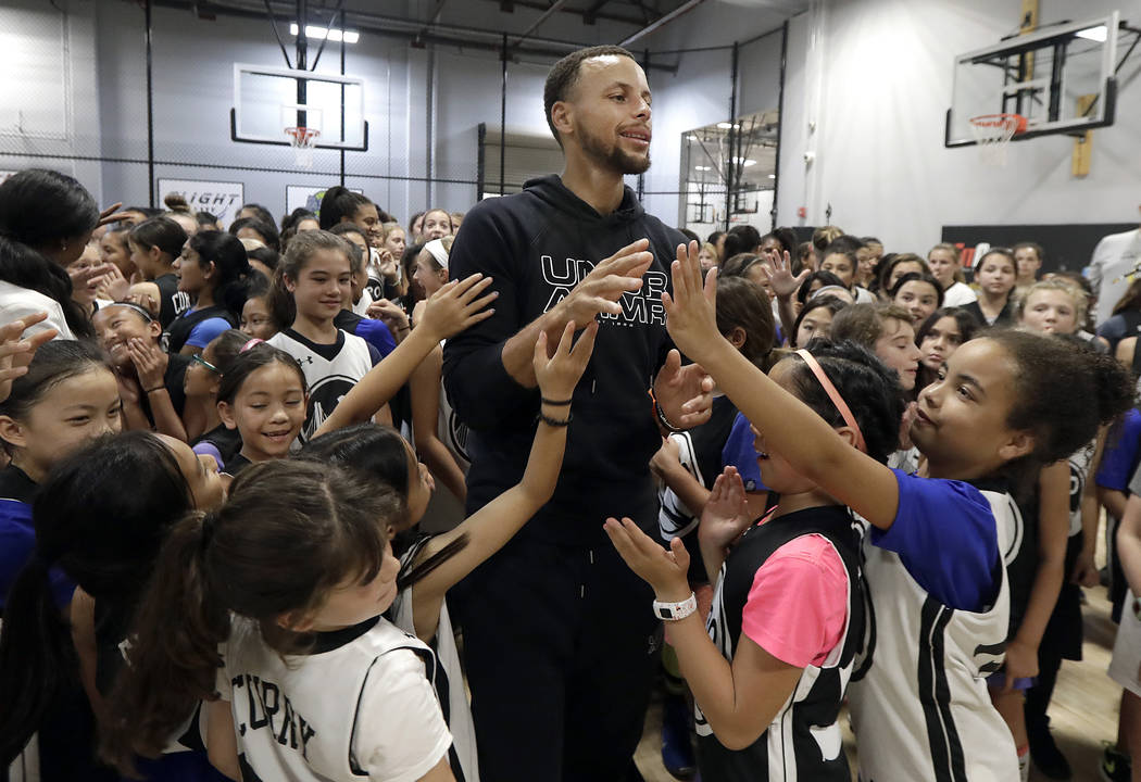 FILE - In this Aug. 14, 2018, file photo, Golden State Warriors' Stephen Curry, center, greets basketball camp participants after taking a group photo at Ultimate Fieldhouse in Walnut Creek, Calif ...