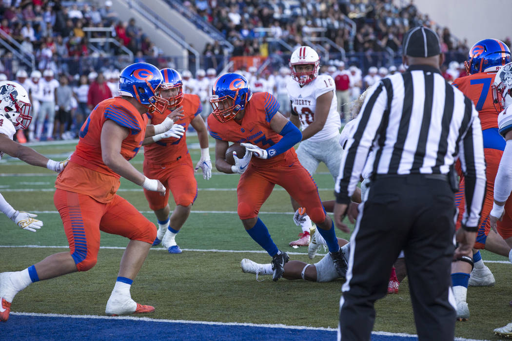Bishop Gorman running back Amod Cianelli (23) breaks through Liberty defenders for a touchdown during the second half of the NIAA 4A Desert Region championship game at Bishop Gorman High School in ...