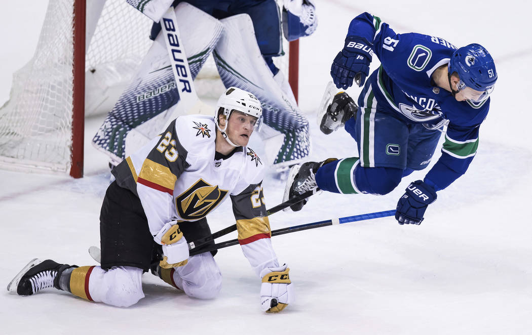 Vancouver Canucks' Troy Stecher, right, is tripped by Vegas Golden Knights' Daniel Carr during the second period of an NHL hockey game Thursday, Nov. 29, 2018, in Vancouver, British Columbia. (Dar ...