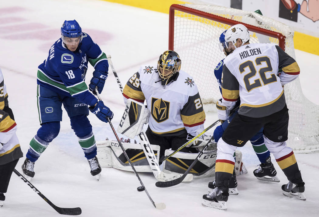 Vancouver Canucks' Jake Virtanen (18) redirects a shot in front of Vegas Golden Knights goalie Marc-Andre Fleury, centre, as Nick Holden (22) and Vancouver's Michael Del Zotto, back right, watch d ...