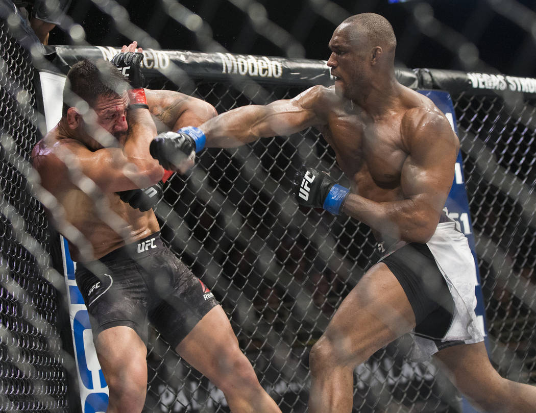 """Kamaru Usman, right, throws a right hook against Rafael dos Anjos in the fifth round during """"The Ultimate Fighter"""" Season 28 Finale on Friday, Nov. 30, 2018, at The Pearl, at Palms, in Las Vegas. ..."""