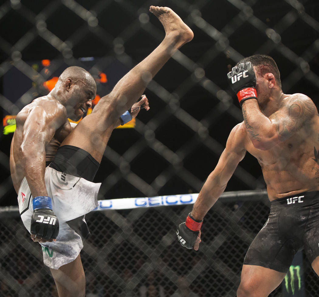 """Kamaru Usman, left, throws a kick against Rafael dos Anjos in the fourth round during """"The Ultimate Fighter"""" Season 28 Finale on Friday, Nov. 30, 2018, at The Pearl, at Palms, in Las Vegas. Usman ..."""