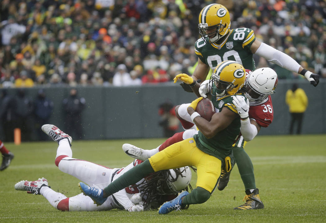 Green Bay Packers wide receiver Davante Adams is hit by Arizona Cardinals strong safety Budda Baker after making a catch during the first half of an NFL football game Sunday, Dec. 2, 2018, in Gree ...