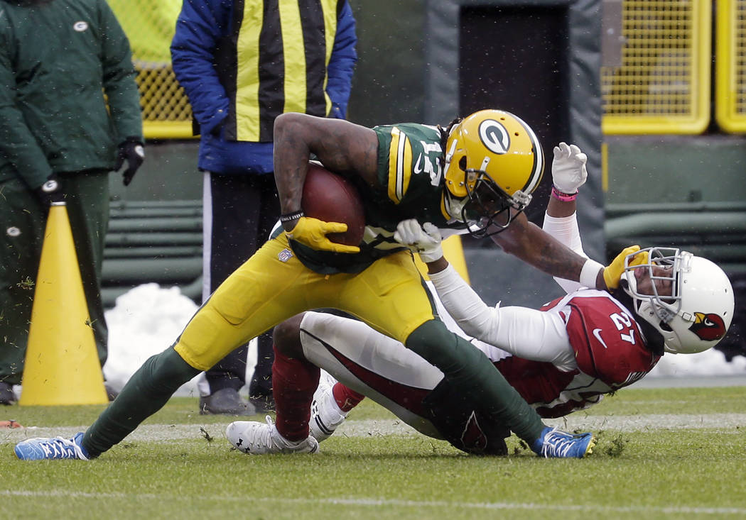 Green Bay Packers wide receiver Davante Adams, left, is hit by Arizona Cardinals defensive back Leonard Johnson, right, after making a catch during the first half of an NFL football game Sunday, ...