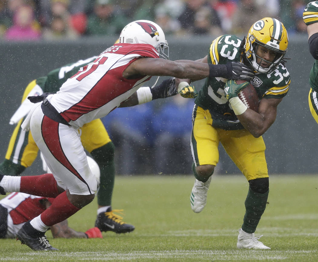 Green Bay Packers running back Aaron Jones is hit on a run play by Arizona Cardinals linebacker Gerald Hodges during the second half of an NFL football game Sunday, Dec. 2, 2018, in Green Bay, Wis ...