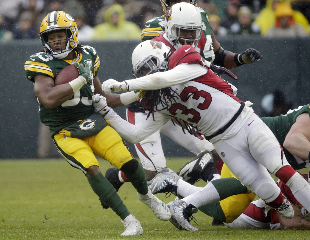 Green Bay Packers running back Aaron Jones is hit during a run by Arizona Cardinals defensive back Tre Boston during the second half of an NFL football game Sunday, Dec. 2, 2018, in Green Bay, Wis ...
