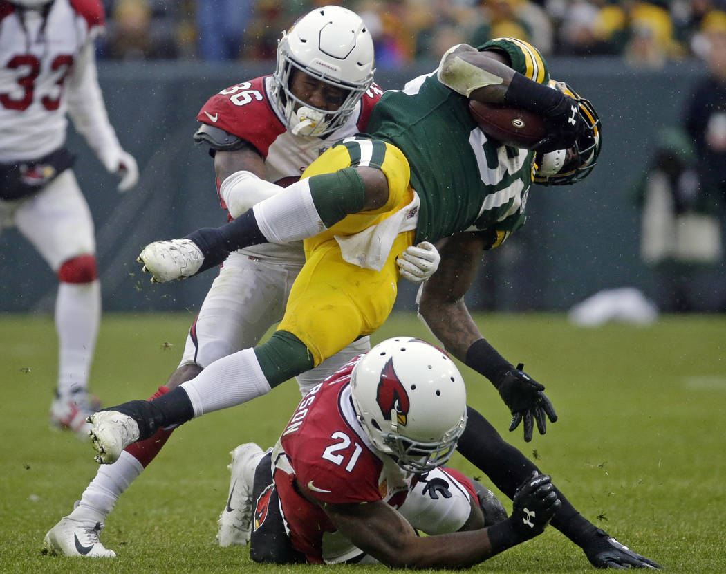 Green Bay Packers running back Jamaal Williams (30) is hit during a run by Arizona Cardinals strong safety Budda Baker (36) and Patrick Peterson (21) during the second half of an NFL football game ...