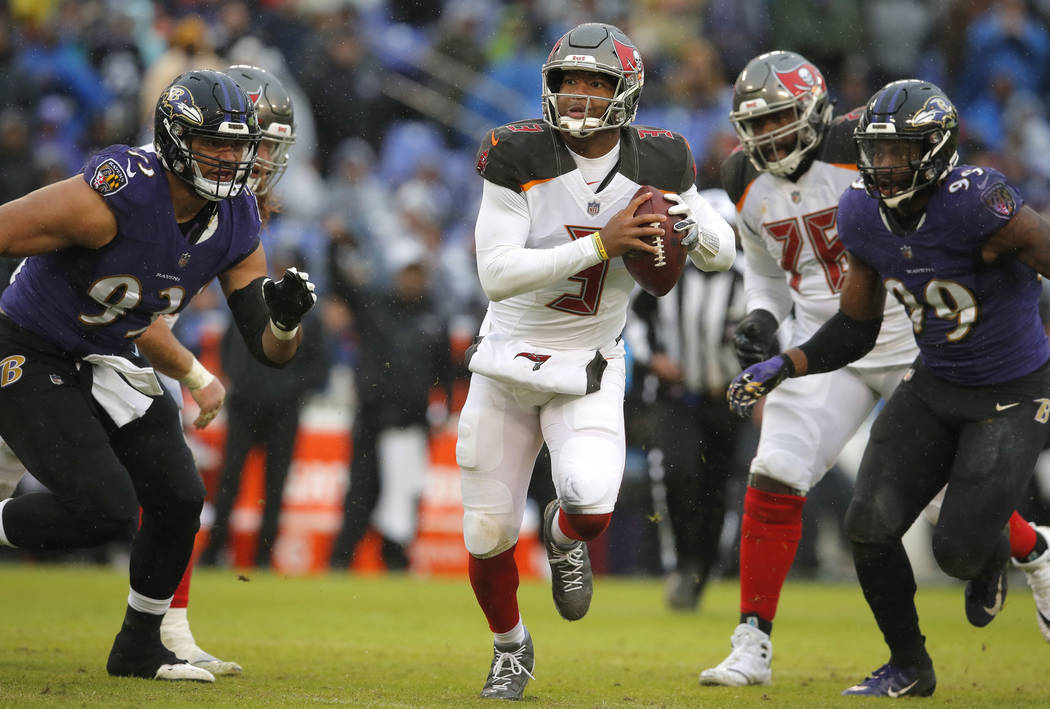 Tampa Bay Buccaneers quarterback Jameis Winston, center, looks for a receiver as he is pressured in the second half of an NFL football game against the Baltimore Ravens, Sunday, Dec. 16, 2018, in ...