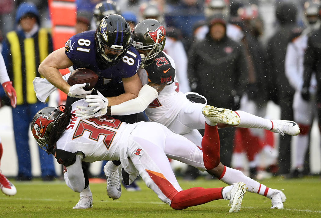 Baltimore Ravens tight end Hayden Hurst (81) is tackled by Tampa Bay Buccaneers cornerbacks Josh Shaw (30) and Ryan Smith in the first half of an NFL football game, Sunday, Dec. 16, 2018, in Balti ...