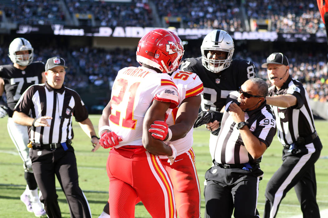 Field Judge James Coleman (95) tries to break up a fight between Oakland Raiders tight end Jared Cook (87) and Kansas City Chiefs strong safety Eric Murray (21) who is held back by outside linebac ...
