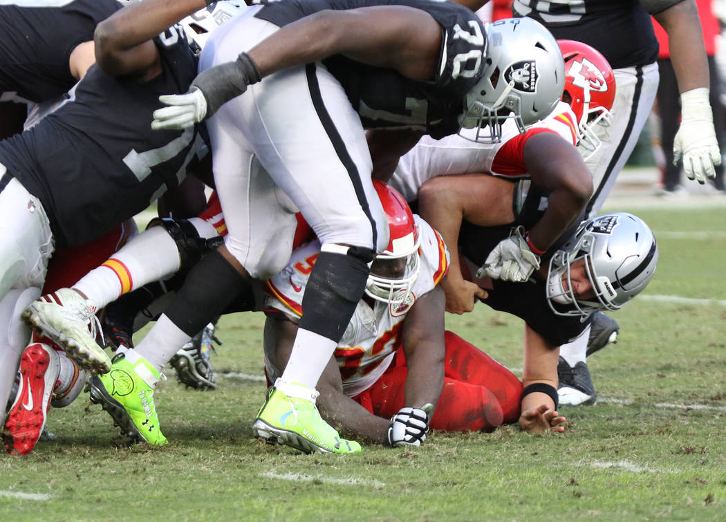 Oakland Raiders quarterback Derek Carr (4) is sacked by Kansas City Chiefs outside linebacker Justin Houston (50) and defensive end Chris Jones (95) during the second half of an NFL game in Oaklan ...