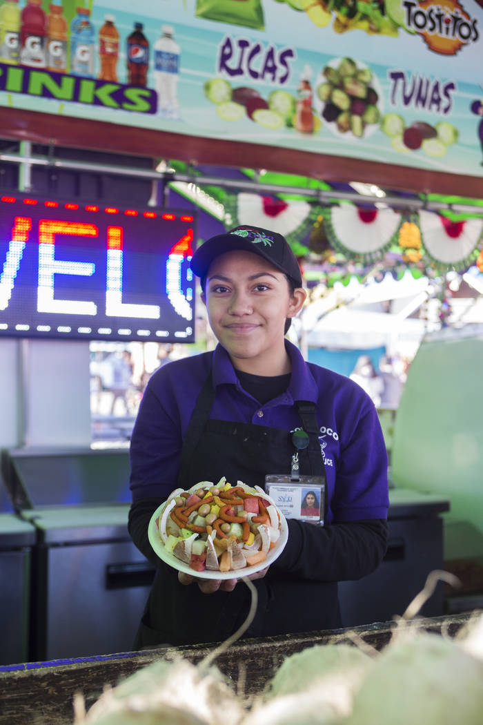 Erika Caro Perez, 16, holds a dish of jicama, watermelon, cucumbers and mango at the Coco Loco stand at Broadacres Marketplace in North Las Vegas, Sunday, Dec. 2, 2018. The family that owns the st ...