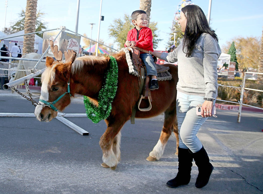 Sandra Arzola of Las Vegas watches her son Adrian, 2, ride a pony during the annual WinterFest event at the Henderson Events Plaza in Henderson, Saturday, Dec. 8, 2018. Erik Verduzco Las Vegas Rev ...