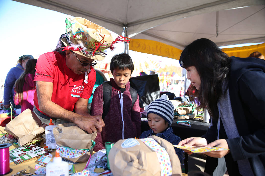 Tony Melendez, from left, helps Ruuku Johnson, 9, his friend Kento Shoji, 4, with his mother Chie Shoji, during the annual WinterFest event at the Henderson Events Plaza in Henderson, Saturday, De ...