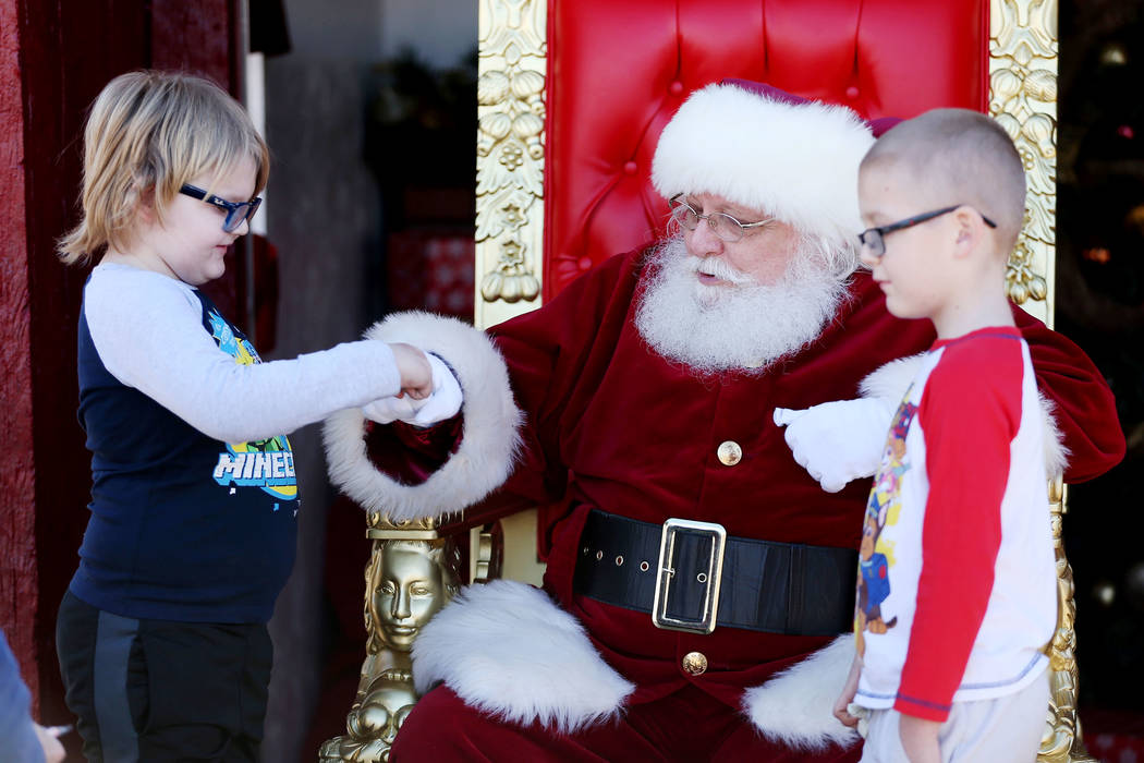 Paxton Wright, left, 6, and his brother Thomas, 7, of Henderson, visit Santa Claus during the annual WinterFest event at the Henderson Events Plaza in Henderson, Saturday, Dec. 8, 2018. Erik Verdu ...