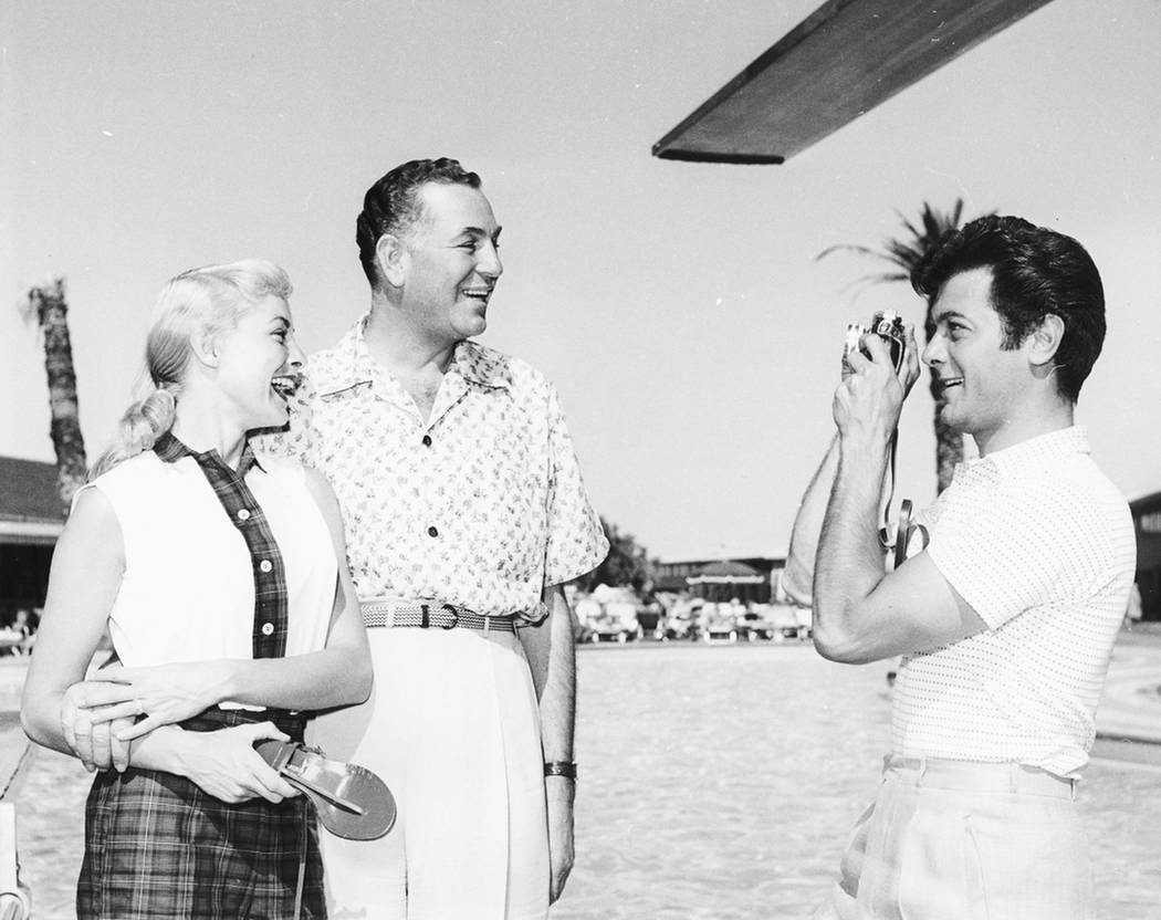 In this 1953 photo, actor Tony Curtis, right, takes a picture of Janet Leigh, left, and Jack Entratter by the Sands Hotel pool in Las Vegas. Curtis, died of cardiac arrest Wednesday Sept. 29, 2010 ...