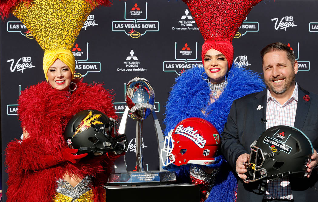 Las Vegas Bowl Executive Director John Saccenti poses for a photo with showgirls Jennifer Autry, left, and Porsha Revesz, center, during a news conference in Las Vegas, Sunday, Dec. 2, 2018, to an ...