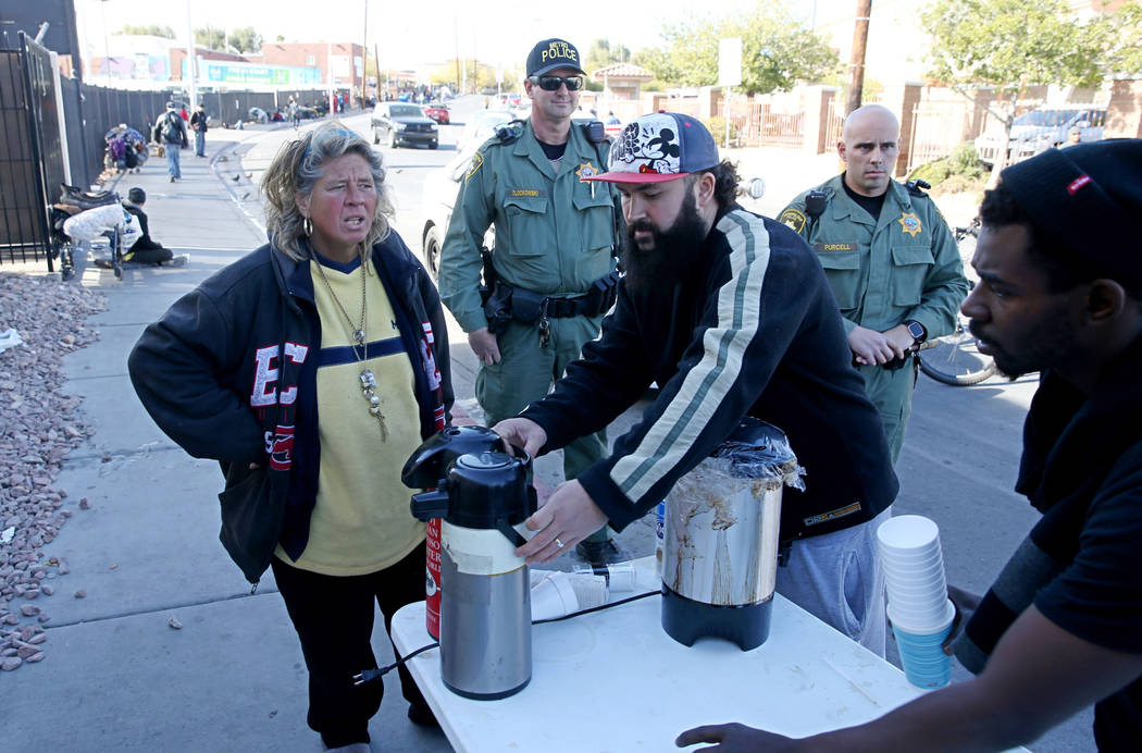 Las Vegas police watch as Joey Lankowski, center, cleans up the area where he was distributing food on Foremaster Lane near Las Vegas Boulevard Wednesday, Nov. 28, 2018. Lankowski was cited for pa ...